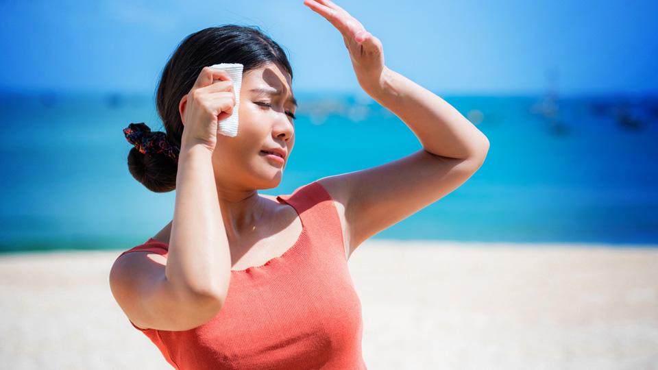 高くなった気温と強い直射日光により体温が上昇して熱中症への懸念をイメージさせる女性の画像