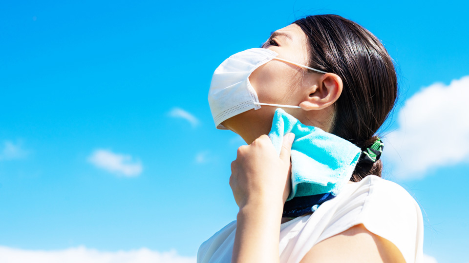 夏の暑い日にマスクを装着して首の汗をぬぐっている画像